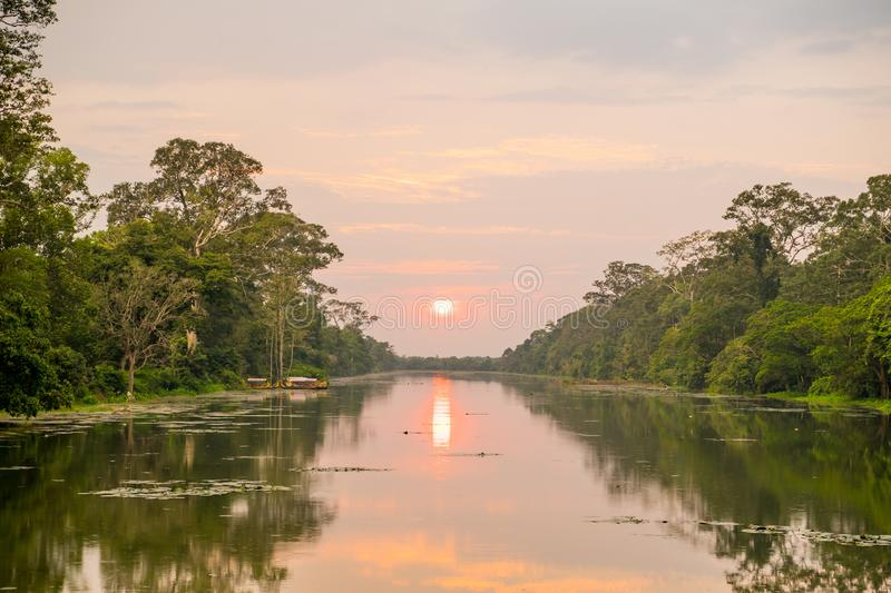 Wild angle shot of sunset above river at angkor wat temple area. Giand starus in the forceground stock images