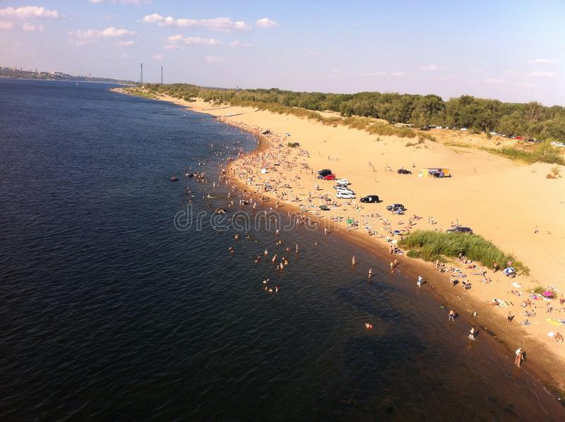Wild beach. On the river Bank. People swim anywhere, cars parked near stock images
