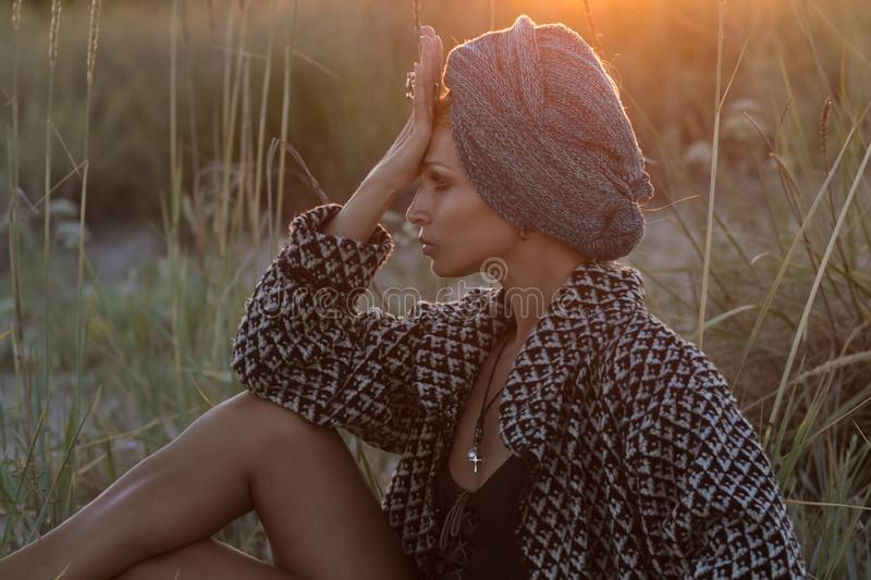 Wild beauty. Luxurious woman in turban posing in african steppe royalty free stock photo