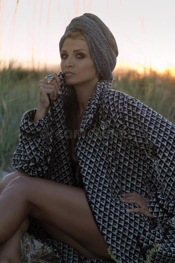 Wild beauty. Luxurious woman in turban posing in african steppe royalty free stock photography