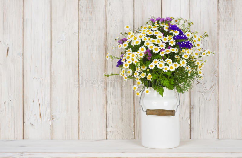 Wild chamomile flowers bouquet on table over wooden planks background royalty free stock image