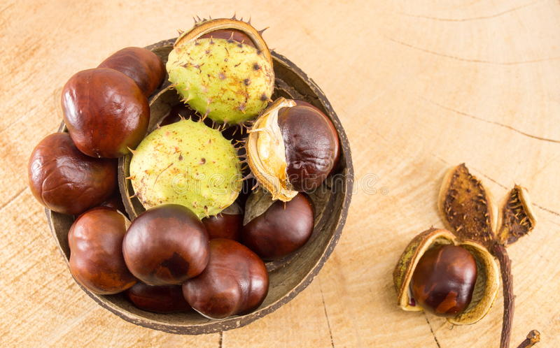 Wild chestnuts on a wooden background stock photo