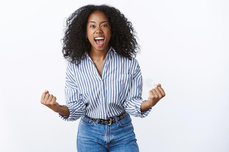 Wild excited overwhelmed attractive african american woman shout out loud happily clench fists victory gesture win. Receive award amazed thrilled celebrate royalty free stock photography
