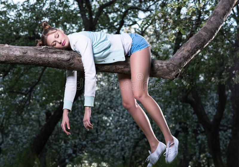 Wild fatigue. Beautiful young woman sleeping on a tree branch. Feet and hands hanging down royalty free stock photo