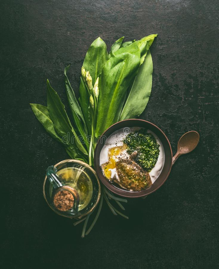 Wild garlic yogurt dip or dressing in wooden bowl on dark rustic kitchen table background with ingredients: oil and mustard,  top. View with copy space. Healthy royalty free stock photos