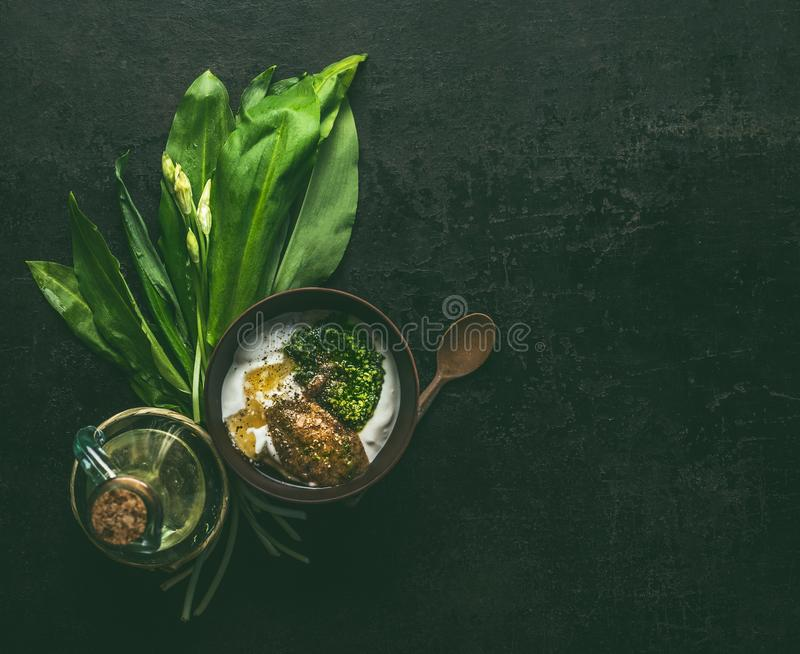 Wild garlic yogurt dip or dressing in wooden bowl on dark rustic kitchen table background with ingredients, top view with copy. Space. Healthy seasonal food royalty free stock images