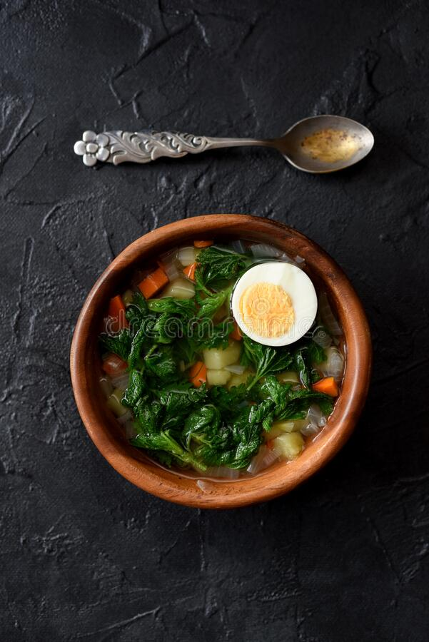 Wild herbs cooking. Rustic style vegetable soup with stinging nettle and boiled egg in wooden bowl with vintage spoon on black. Background top view copy space stock photography