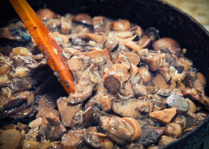 Wild mushrooms and onions fried in a cooking pan royalty free stock image
