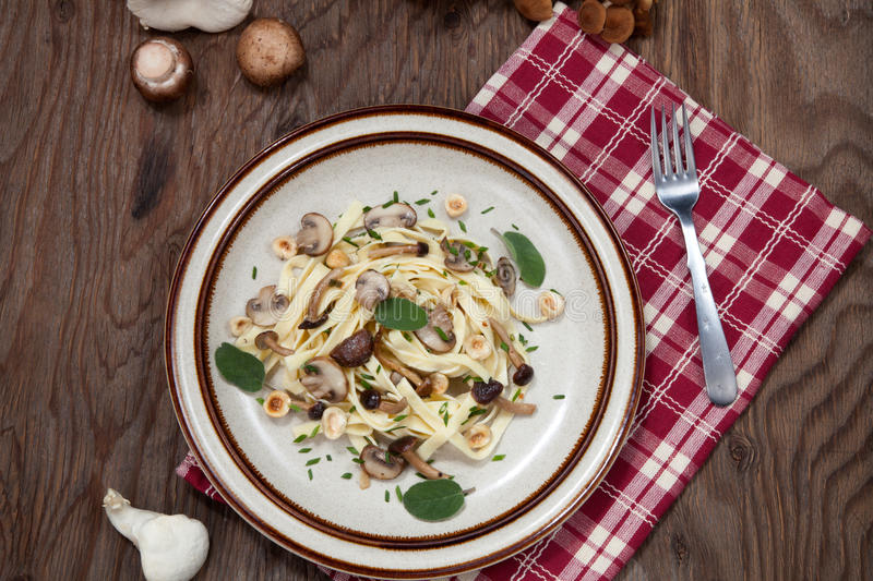 Wild Mushrooms Pasta. Wild mushrooms Linguini pasta with roasted hazelnut, sage, and chives stock photography