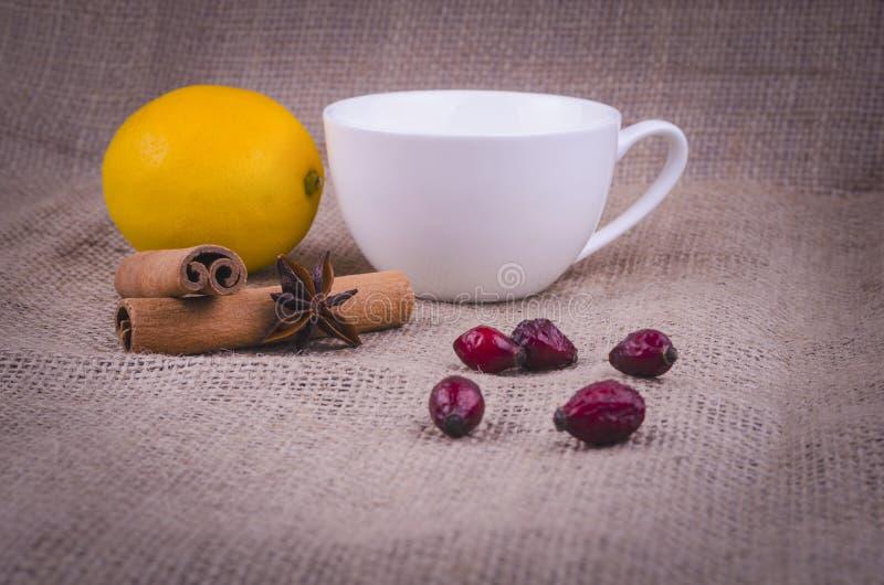 Wild nam, pijpjes kaneel, anijsplant en citroen op de achtergrond van jute met een witte kop toe stock foto