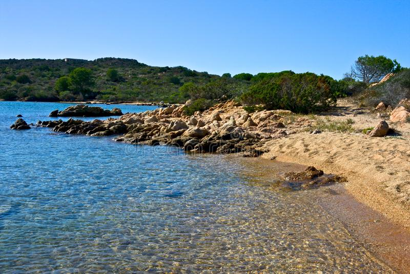 Wild nature seascape with blue water, sandy beach with some rocks royalty free stock images