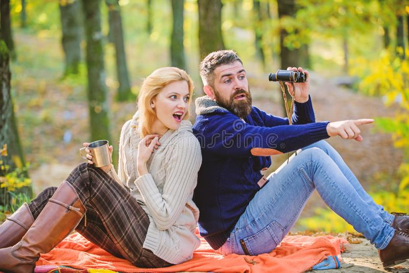 Wild outdoor. couple in love relax in autumn forest with tea or coffee. camping and hiking. surprised girl drink mulled. Wine. bearded men shocked watch with stock images