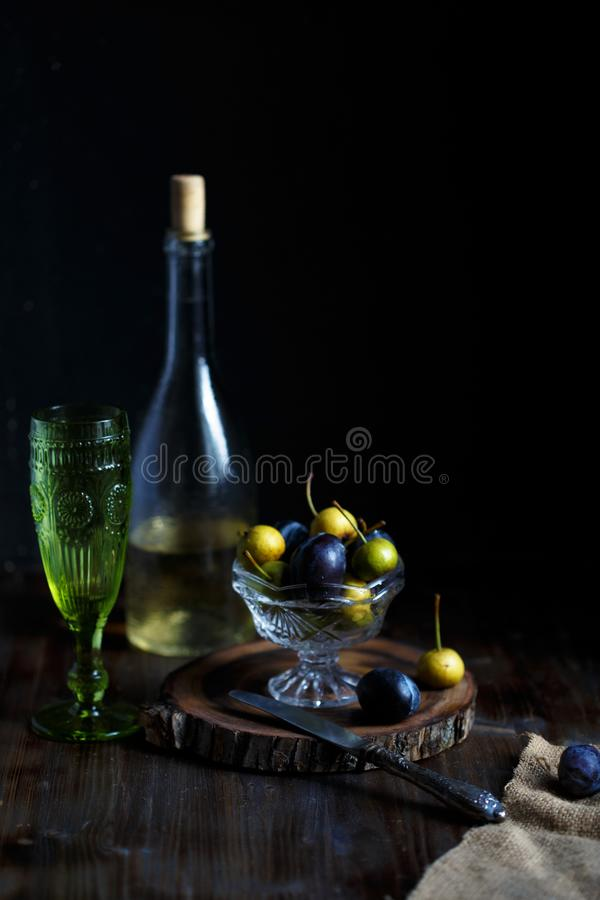 Wild pear and plum in a glass bowl, a glass and a bottle of homemade pear wine on a wooden close background. Rustic concept. royalty free stock images