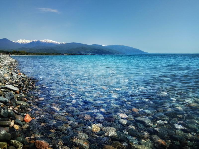 Wild pebble beach view with blue sky and mountains stock photography