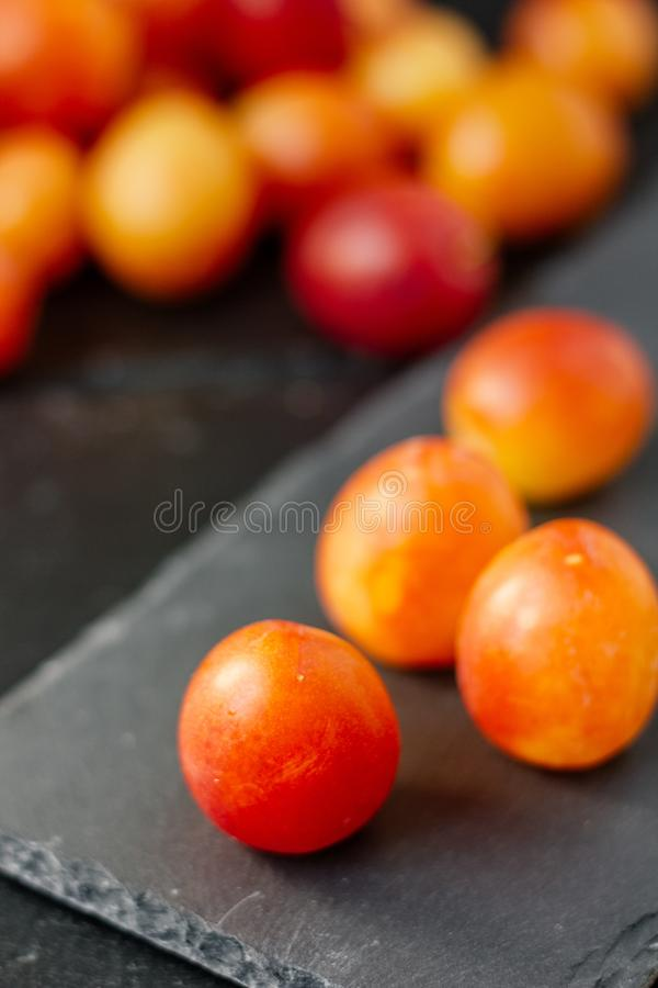 Wild plums fruits on black stone board. Wild plums fruits on black stone board stock photos