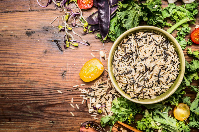 Wild rice with kale and vegetables ingredients for healthy cooking on rustic wooden background stock image