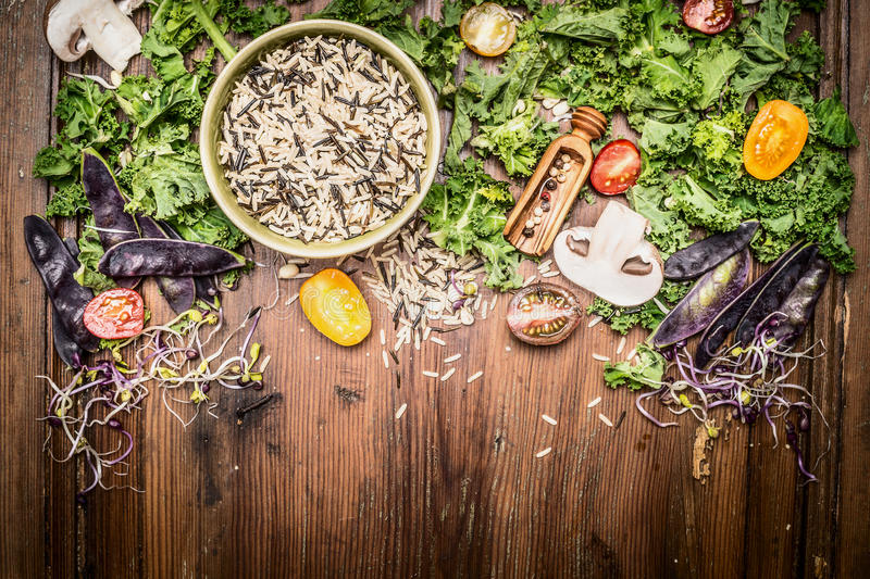 Wild rice with kale and vegetables ingredients for tasty cooking on rustic wooden background stock photography