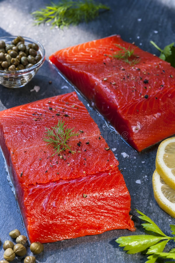 Wild salmon steaks. Two pieces of raw wild salmon fish steaks with lemon, capers and herbs, ready to cook stock photography