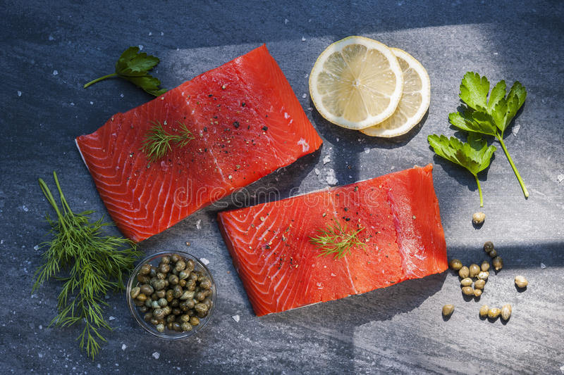 Wild salmon steaks. Two pieces of raw wild salmon fish steaks with lemon, capers and herbs, ready to cook, from above royalty free stock image
