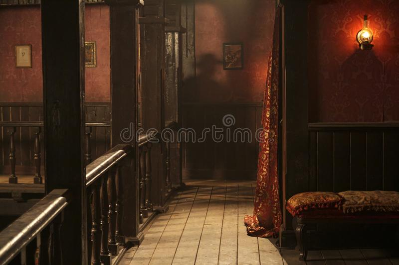 Wild sest saloon upper floor with a man& x27;s shadow. Western town saloon upper floor view with shadow of a man behind a pillar and gas light and wallpaper and royalty free stock photography