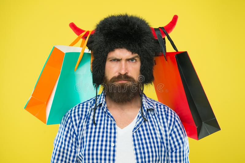 Wild about shopping. Shopping concept. Guy shopping sales season with discounts. Full packages of items. Man strict face. Wear hat of bull with horns. Hipster royalty free stock photos