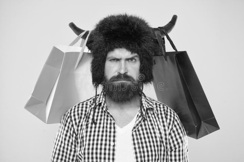 Wild about shopping. Shopping concept. Guy shopping sales season with discounts. Full packages of items. Man strict face. Wear hat of bull with horns. Hipster stock photography