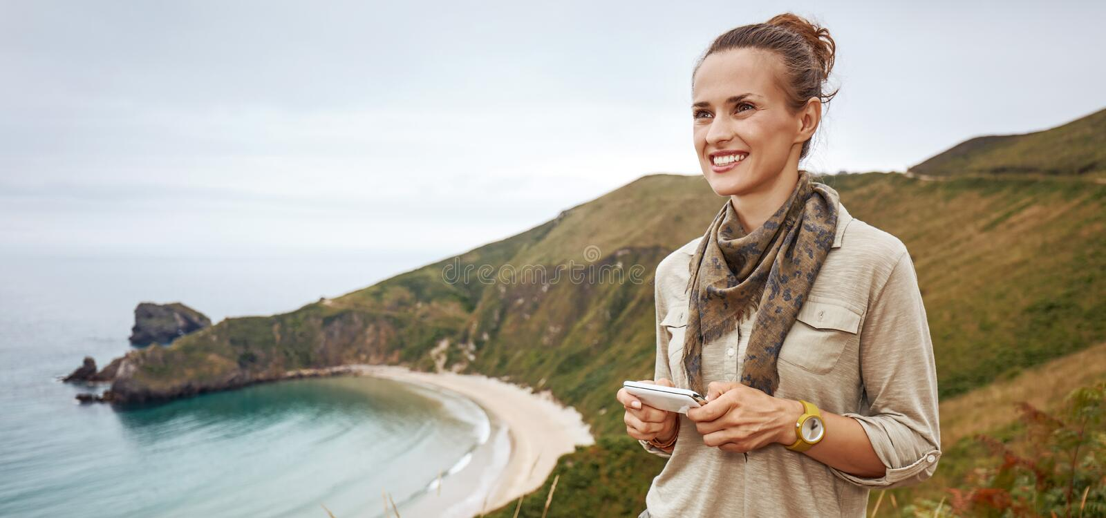 Happy woman hiker writing sms in front of ocean view landscape. Into the wild in Spain. happy adventure woman hiker writing sms in front of ocean view landscape royalty free stock image