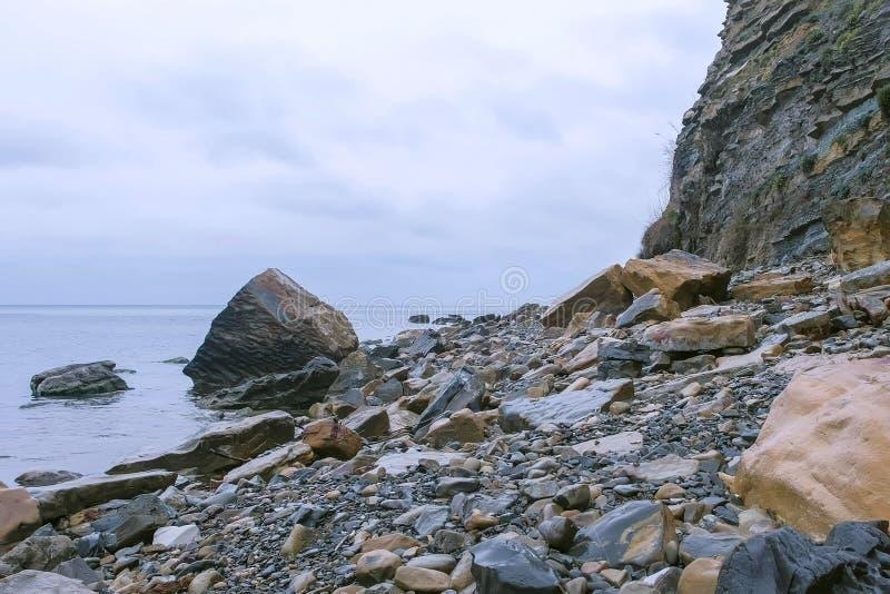 Wild stony beach with huge cliff on rainy day on sea coast. royalty free stock image