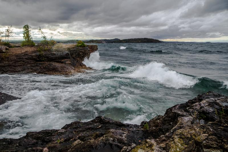 Wild And Stormy Lake Superior Coast. Lake Superior waves crash on the cliffs of Presque Isle Park in Marquette, Michigan. Referred to as the Inland Sea, Lake stock photo