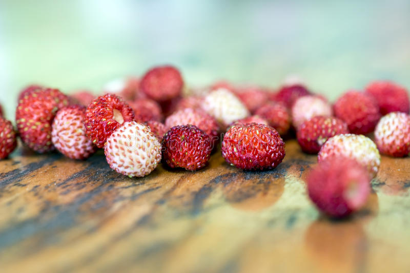 Wild strawberries on an old wooden table royalty free stock image