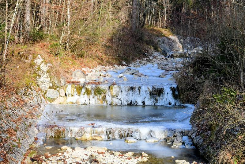 Wild stream in the mountains of austria in winter with snow and ice. Wild stream mountains Austria winter snow ice Cold trees forest royalty free stock photos