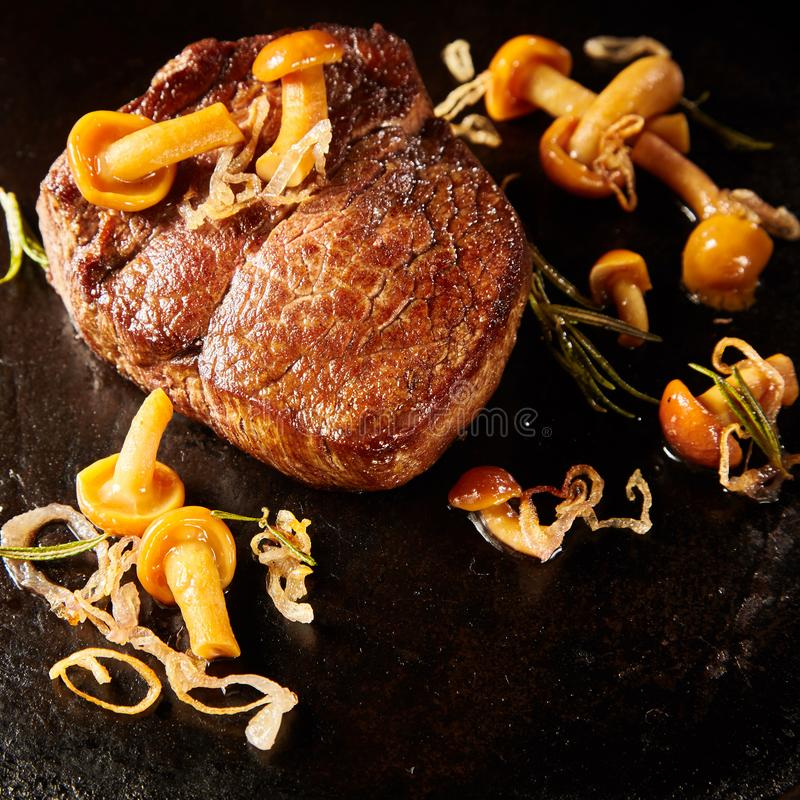 Wild venison game steak served with mushrooms. Thick marinated lean wild venison game steak served with autumn forest mushrooms, rosemary and fried onion on stock photo