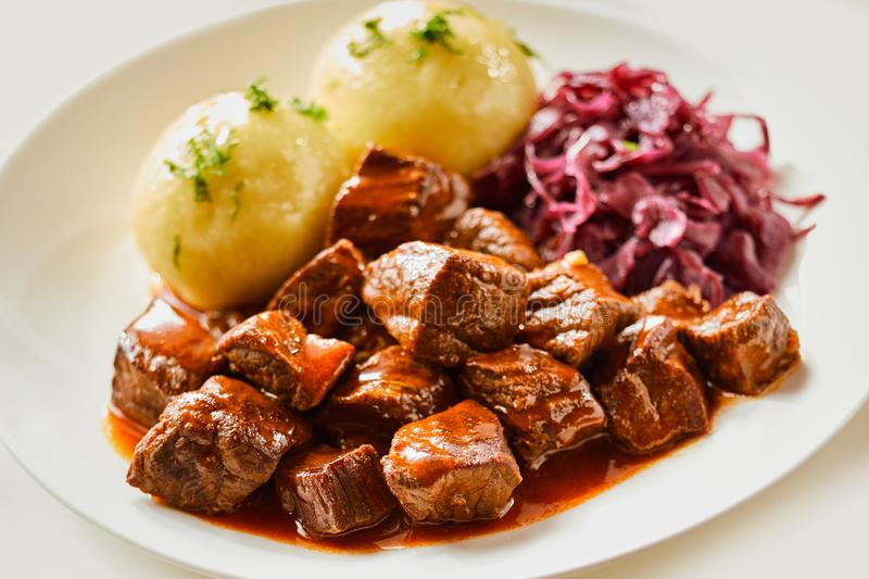 Wild venison goulash or hot pot. Served with dumplings and red cabbage in a close up side view for advertising royalty free stock photo