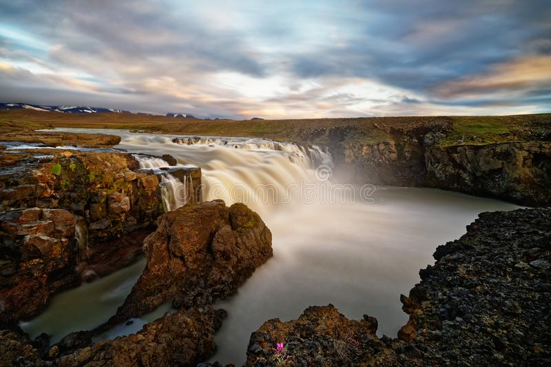 Waterfall in wild landscape in the evening light stock images