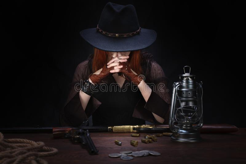 wild west girl with revolver gun sitting at the table with ammunition and silver coins royalty free stock photo