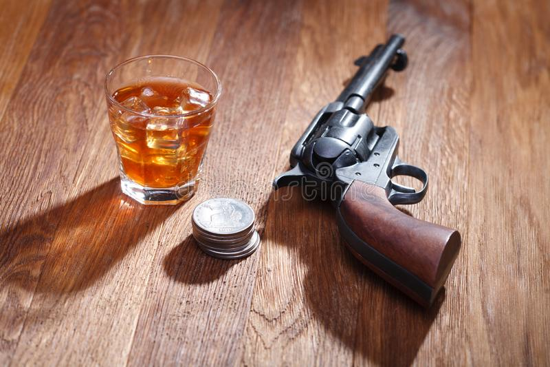 Wild west revolver with glass of whisky and ice with old silver dollar on wooden table royalty free stock photo