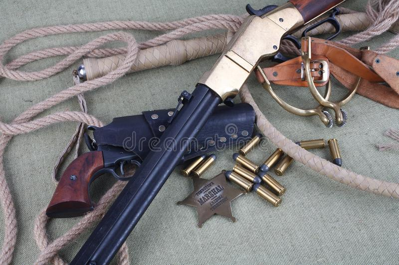 Wild west rifle, ammunition and sheriff badge royalty free stock photography