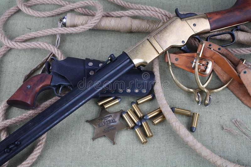 Wild west rifle, ammunition and sheriff badge royalty free stock photo