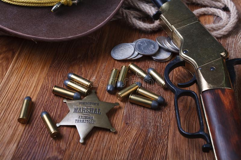 Wild west rifle, ammunition and sheriff badge. On wooden table royalty free stock photography