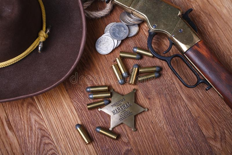 Wild west rifle, ammunition and sheriff badge. On wooden table stock photography