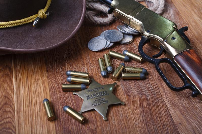 Wild west rifle, ammunition and sheriff badge. On wooden table stock image