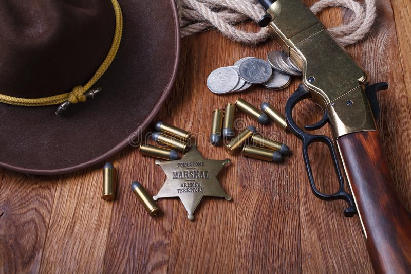 Wild west rifle, ammunition and sheriff badge. On wooden table stock images