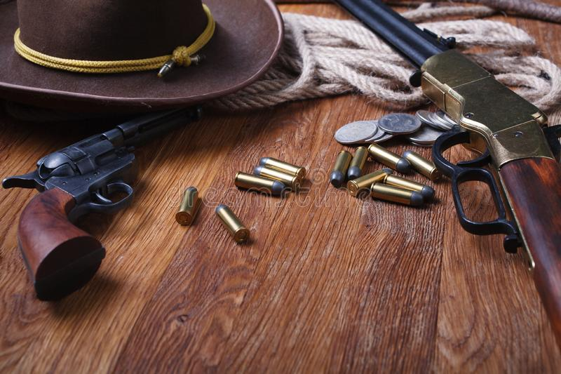 Wild west rifle, ammunition and sheriff badge. On wooden table royalty free stock image
