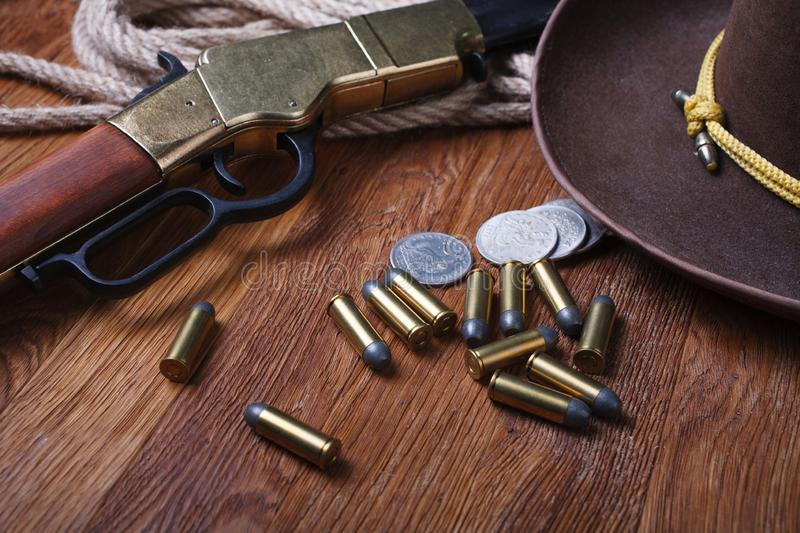 Wild west rifle, ammunition and sheriff badge. On wooden table royalty free stock photo