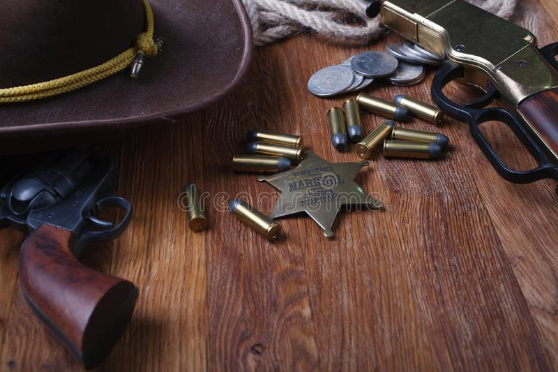 Wild west rifle, ammunition and sheriff badge. On wooden table royalty free stock images