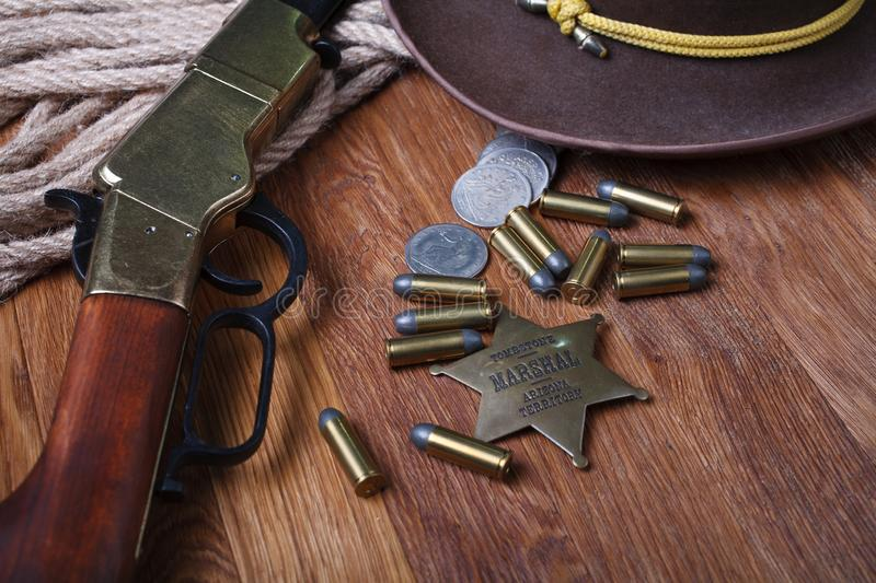 Wild west rifle, ammunition and sheriff badge. On wooden table stock photos