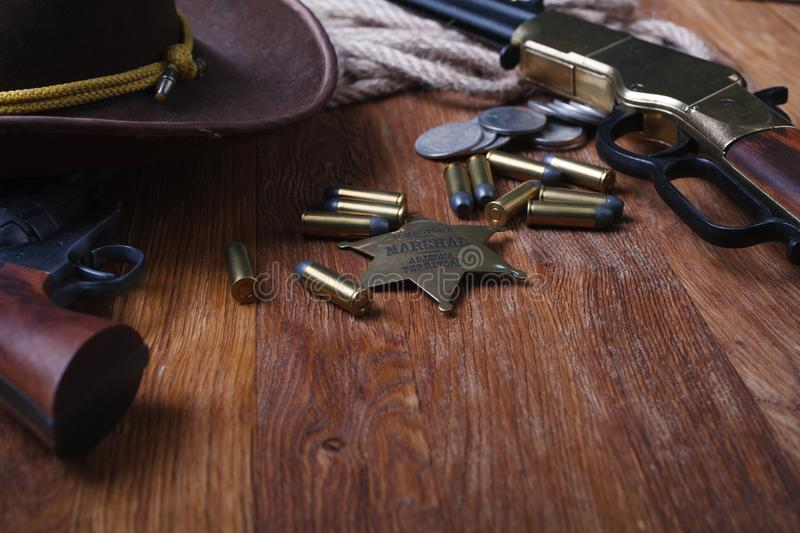 Wild west rifle, ammunition and sheriff badge. On wooden table stock photo