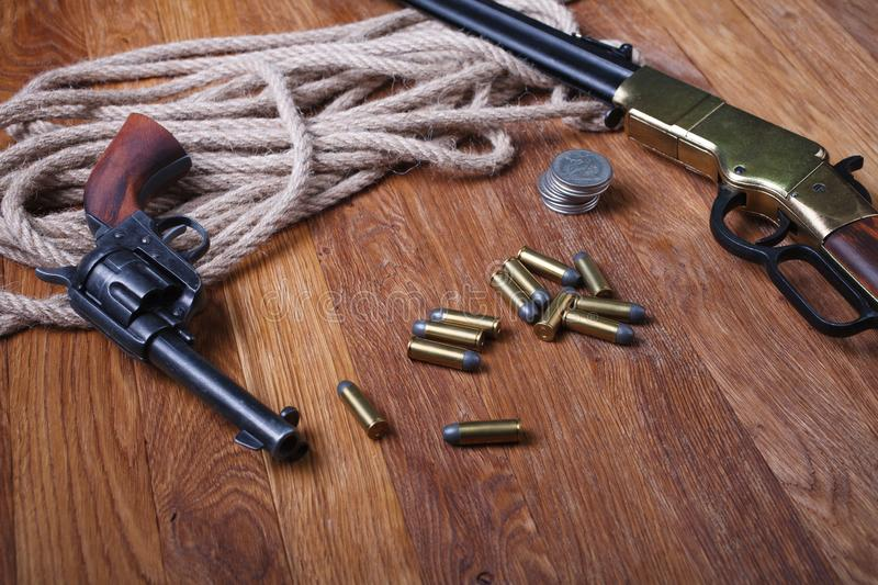 Wild west rifle, ammunition and silver dollars. On wooden table stock image