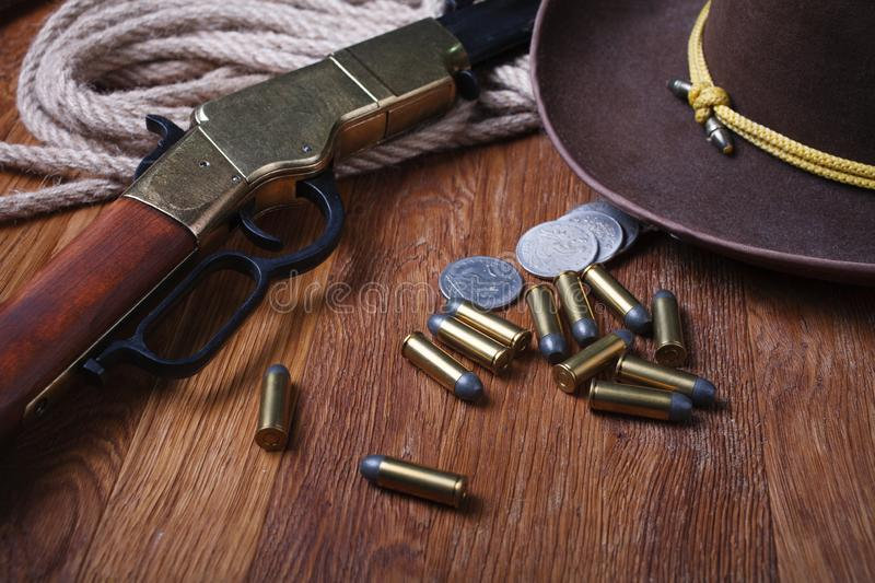 Wild west rifle, ammunition and silver dollars. On wooden table stock photo