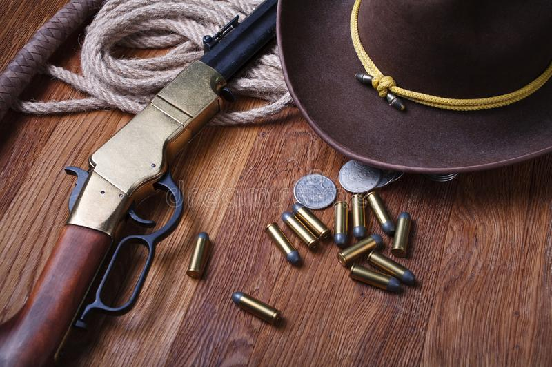Wild west rifle, ammunition and silver dollars. On wooden table stock photography